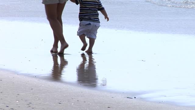 mamma e figlio a piedi al mare - fianco a fianco video stock e b–roll