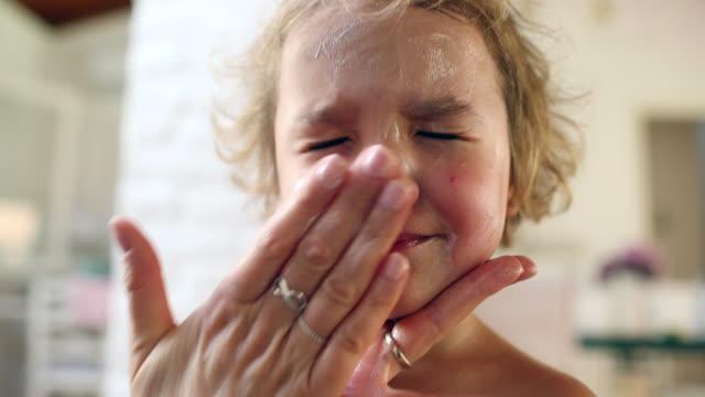 vídeos de stock e filmes b-roll de mom applying sunscreen lotion to toddler boy face - protetor solar