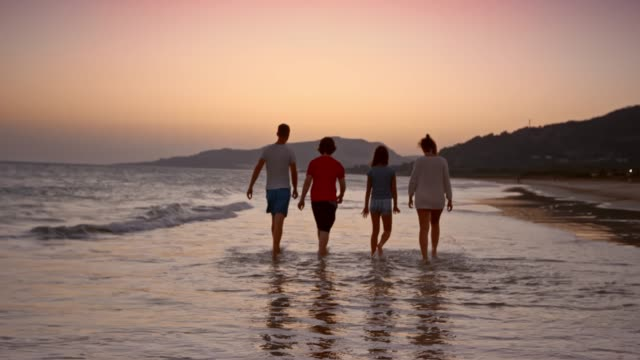 SLO MO Mom, dad and two teenage kids walking on the beach at sunset