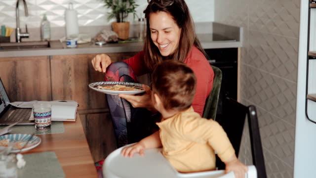 stockvideo's en b-roll-footage met moeder eten haar ontbijt en praten met haar peuter zoon - omgeving