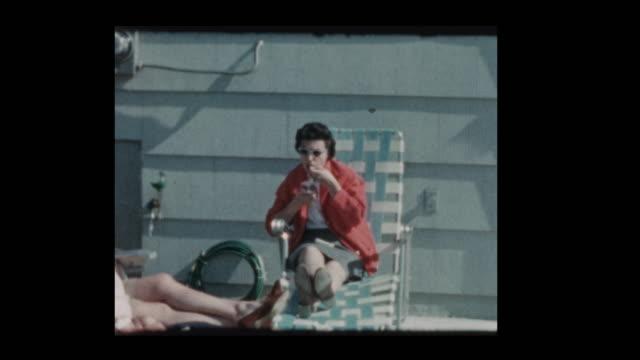 1961 mom eats ice cream while little boy in red sweater running around backyard - hotel reception filmów i materiałów b-roll