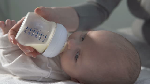 Mom feeds the baby with formula from a bottle. Family, concepts of motherhood. video