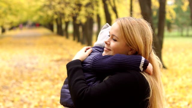 Mom gently hugs her son in the autumn Park. video