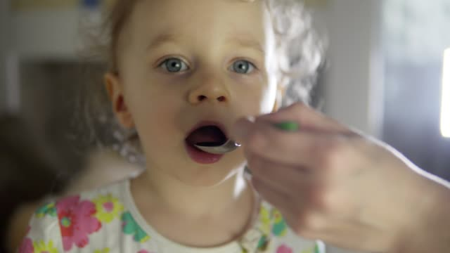 Mom giving the child a cough syrup. 4k Mom giving the child a cough syrup. 4k spoon stock videos & royalty-free footage