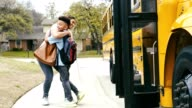 istock Mom greets son after he gets off of school bus 1215745421