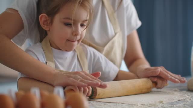mamma hjälper dotter att rulla ut deg. mamma och lilla dotter rulla ut degen för att göra kakor. med brödkavel och tillverkning av kex. - enbarnsfamilj bildbanksvideor och videomaterial från bakom kulisserna