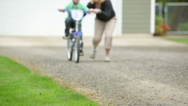 Mom helping son ride bicycle video