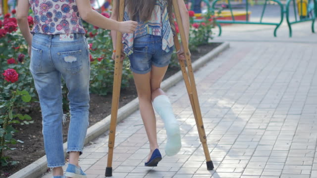 Mom helps my daughter with a broken leg on crutches to walk along the street A girl with a broken leg with the help of crutches and mother moves along the street crutch stock videos & royalty-free footage