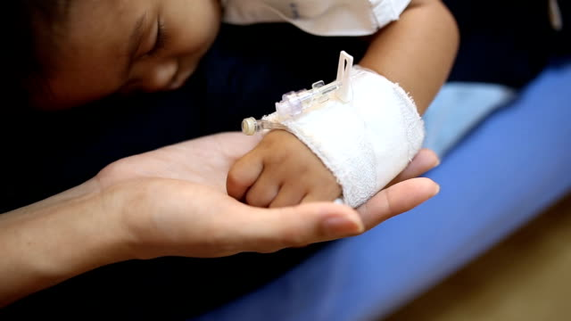 Mom holding sick baby's hand, HD. video