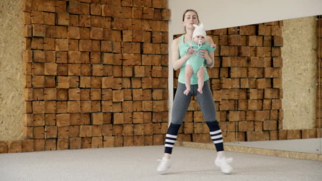Mom holds the baby in her arms and jumps during fitness video