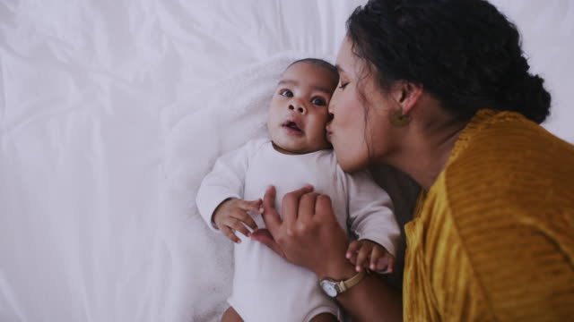 Mom is always there to make everything better 4k video footage of a young woman lying on bed with her baby kissing stock videos & royalty-free footage