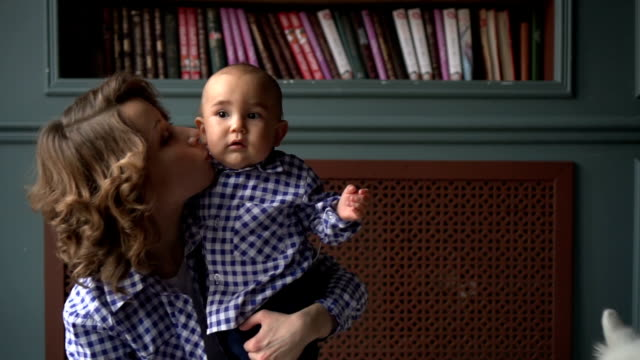 mom is holding a one-year-old boy in her arms. mom and son in identical shirts - abbigliamento da neonato video stock e b–roll