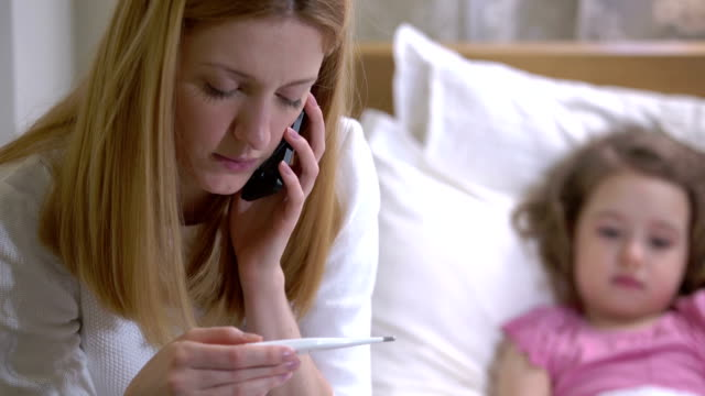Mom is measure the temperature of little girl and call the doctor. video