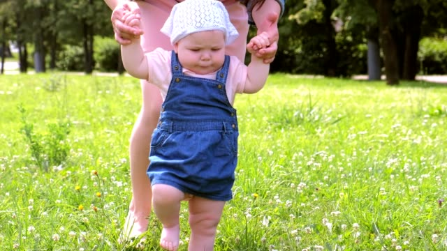 Mom learning baby girl to walk, first steps in park with barefooted legs. video