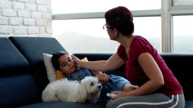 vídeos de stock e filmes b-roll de mom measuring fever to sick little girl with thermometer - doença