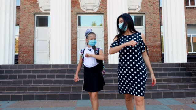 mom meets daughter from school in schoolyard. schoolgirl and woman, are both in protective masks. Back to school after covid19 outbreak. Greetings in Covid-19 time video