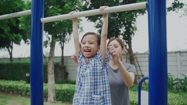stockvideo's en b-roll-footage met het spelen van de mamma met dochter op speelplaats in park - aziatische etniciteit