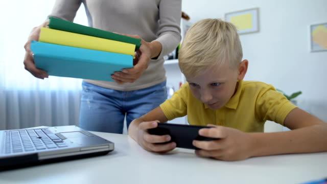 stockvideo's en b-roll-footage met moeder zetten boeken op tafel, ondeugende jongen spelen smartphone in plaats van huiswerk - kids online abuse