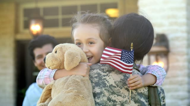 Mom returns home from overseas military assignment Excited mid adult mom returns home from overseas military assignment. She embraces her adorable preschool age daughter upon her return. The little girl is holding a stuffed toy dog and a small American flag. The soldier's husband is smiling in the background. veteran stock videos & royalty-free footage
