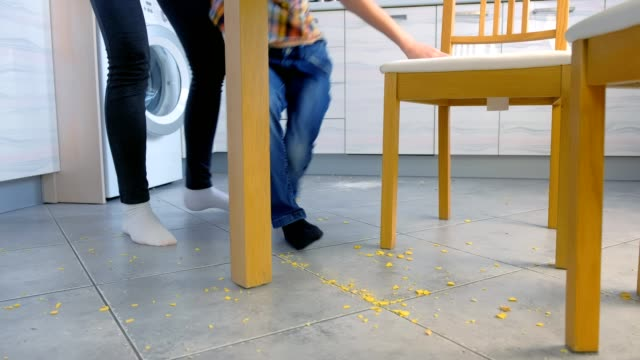 Mom scolds her son for scattered food on the kitchen floor and makes him clean up. Clean up corn flakes off the floor together. video