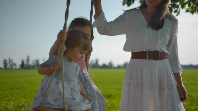 Mom shakes two small sisters, 1 and 3 years old, on a wooden swing with rope handles