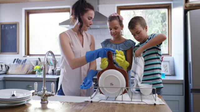 Mom shouldn't be doing dishes alone! 4k video footage of two young children helping their mother with the dishes at home washing dishes stock videos & royalty-free footage