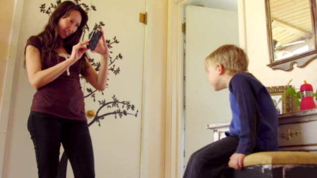 Mom take pictures of son using mobile phone video