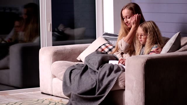 Mom teaching daughter to read at home video