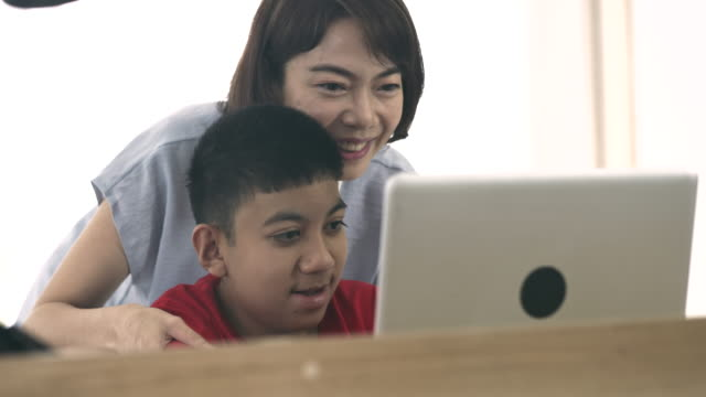 Mom teaching her disabled boy using laptop at home Female caregiver helping to disabled boy(10-11 years) education on laptop computer at home. Asian disabled boy in wheelchair homeschooling with his mother. 4K Resolution autism stock videos & royalty-free footage