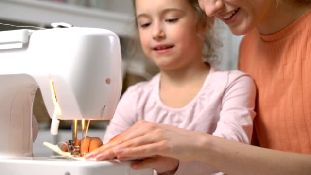 mom teaching her little daughter to sew using a sewing machine in the nursery at home - sarta video stock e b–roll