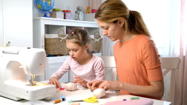 mom teaching her little daughter to sew using needle and thread - sarta video stock e b–roll