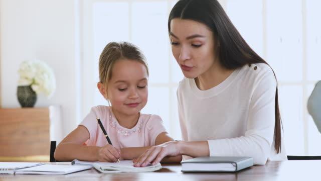 vidéos et rushes de le tuteur de maman enseigne aident la fille d'enfant apprendre à écrire faisant des devoirs - enfant d'âge pré scolaire