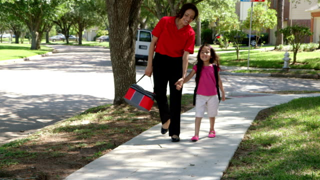 mom walking her young daughter home from school video