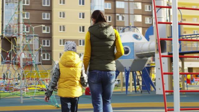 mama zu fuß in richtung spielplatz mit kind - kinderspielplatz stock-videos und b-roll-filmmaterial
