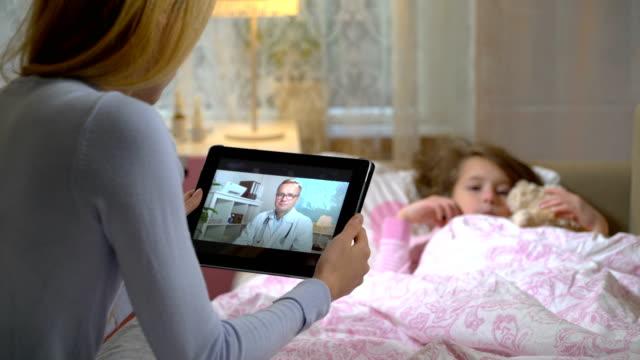 vídeos y material grabado en eventos de stock de mamá con una hija enferma obtiene la consulta de un doctor utilizando el chat de video en casa. - afección médica