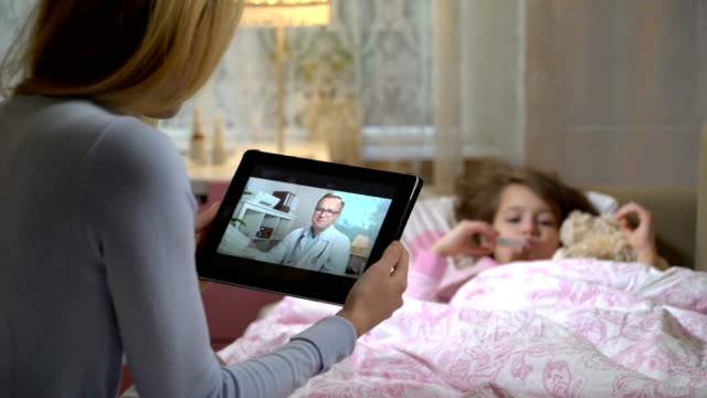 mom with a little sick daughter gets a doctor's consultation using video chat at home. - telemedicine stock videos & royalty-free footage