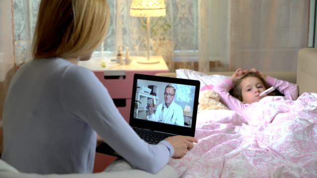 mamma med en liten sjuk dotter får ett läkarbesök som använder videochatt hemma. - videor med medicinsk undersökning bildbanksvideor och videomaterial från bakom kulisserna