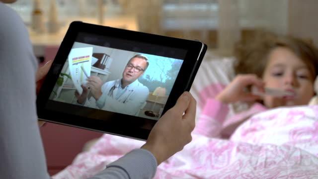 病気の娘を持つお母さんは、家でビデオ チャットを使用して、医師の相談を取得します。 - 人里離れた点の映像素材/bロール