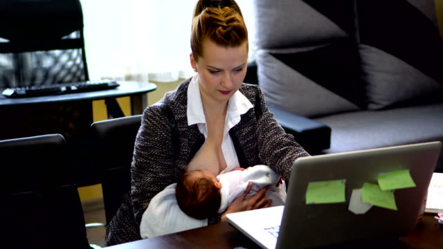 vídeos de stock e filmes b-roll de mom with baby working from home - amamentação