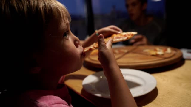 vídeos de stock e filmes b-roll de mom with children chooses pizza in a cafe and have a fun - pizza