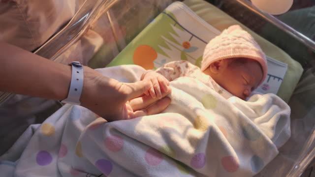 Mom with cute sleeping newborn in hospital