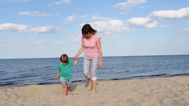 mom with little child on sea shore - eastern european descent stock videos & royalty-free footage