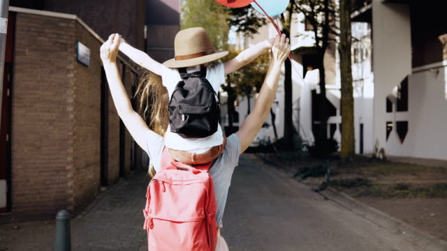 mom with son on shoulders walk holding hands. happy woman carries a kid in hat and two air balloons. lifestyle 4k - viaggiare zaino in spalla video stock e b–roll