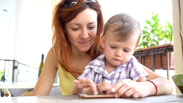 mom with son use a smartphone for Internet video