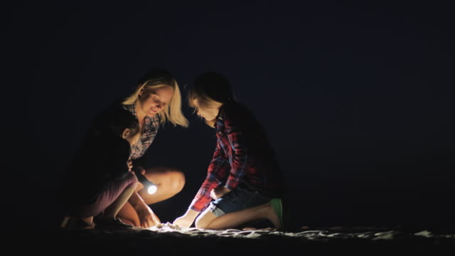 Mom with two daughters playing in the sand on the beach in the late evening. They light the ground with a flashlight. Adventure and Quest Concept Mom with two daughters playing in the sand on the beach in the late evening. They light the ground with a flashlight. Adventure and Quest Concept. flashlight stock videos & royalty-free footage