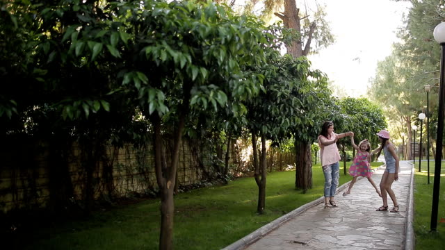 Mom with two daughters walks along the avenue with orange trees video