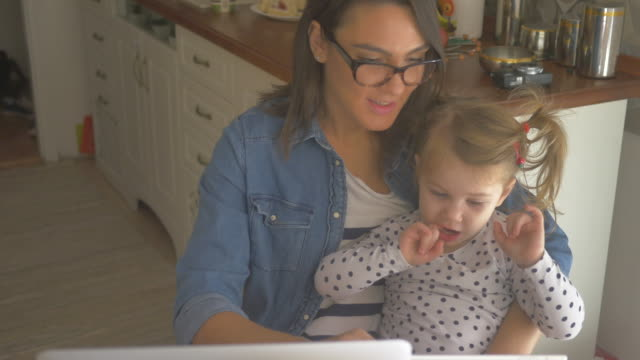 Mom working from home 4K Video of a young mother and her daughter, sitting at their kitchen. Mom, who is working from home, is trying to entertain her kid with a cartoons on a digital tablet (4k resolution) life balance stock videos & royalty-free footage