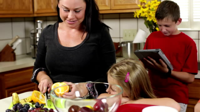 Mom working in the kitchen with kids