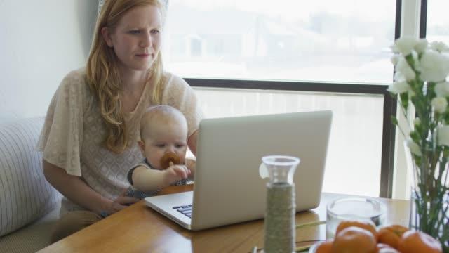 stockvideo's en b-roll-footage met moeder werkt op haar computer terwijl haar baby baby in haar schoot - student