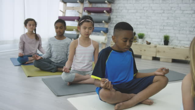 Moment of Peace A small multi-ethnic group of elementary age children is participating in an indoors yoga class. They are meditating with their eyes closed on yoga mats. There is a sense of unity, harmony, and inspiration. mindfulness stock videos & royalty-free footage